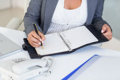 Businesswoman writing on book Stock Photography