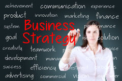 Businesswoman writing business strategy concept. Blue background. Royalty Free Stock Photos