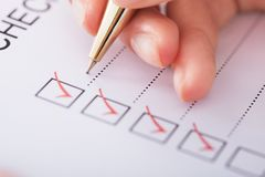 Businesswoman writing on checklist Stock Photography