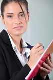Businesswoman writing on clip-board Royalty Free Stock Photos