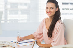 Businesswoman writing on clipboard at a bright office Stock Photography