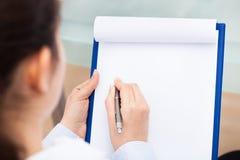 Businesswoman writing on clipboard Stock Photos