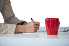 Businesswoman writing on clipboard with coffee mug on desk Royalty Free Stock Photos