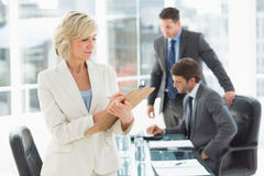 Businesswoman writing on clipboard with colleagues in background Royalty Free Stock Photo