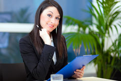 Businesswoman writing on a clipboard Stock Photo