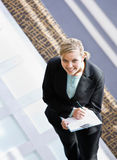 Businesswoman writing on clipboard in office. High angle view of businesswoman writing on clipboard in office lobby Royalty Free Stock Photo