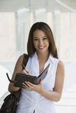 Businesswoman Writing In Day Planner Royalty Free Stock Photo