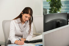 Businesswoman Writing At Desk Stock Image