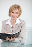 Businesswoman writing in diary Royalty Free Stock Image