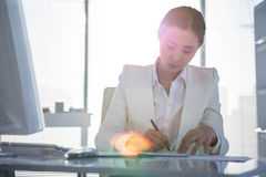 Businesswoman writing on diary on desk Royalty Free Stock Photography