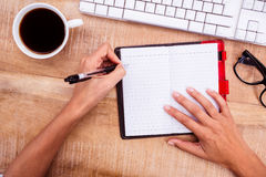 Businesswoman writing on diary on desk Stock Images