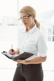 Businesswoman writing in diary at office Stock Photography