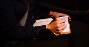 Businesswoman writing in diary while travelling in car stock video