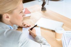 Businesswoman writing documents with pen. Thoughtful mature businesswoman writing documents with pen at workplace stock image