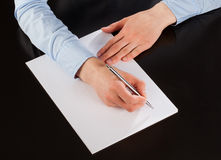 Businesswoman writing down notes on the paper (signing a documen Stock Photos