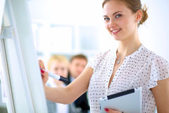 Businesswoman writing on flipchart while giving Royalty Free Stock Photography