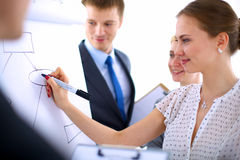 Businesswoman writing on flipchart while giving Stock Photo
