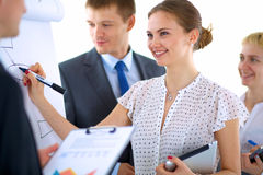 Businesswoman writing on flipchart while giving Stock Photography