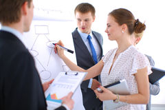 Businesswoman writing on flipchart while giving Stock Images