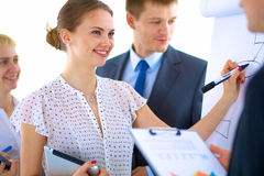 Businesswoman writing on flipchart while giving Royalty Free Stock Photos