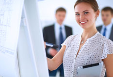 Businesswoman writing on flipchart while giving Stock Image
