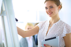 Businesswoman writing on flipchart while giving presentation to colleagues in office Royalty Free Stock Photo
