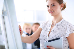 Businesswoman writing on flipchart while giving presentation to colleagues in office Royalty Free Stock Image