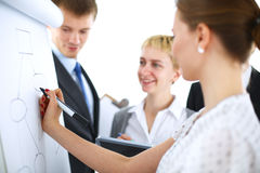 Businesswoman writing on flipchart while giving presentation to colleagues in office Royalty Free Stock Photos