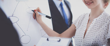 Businesswoman writing on flipchart while giving presentation to colleagues in office Royalty Free Stock Images