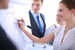 Businesswoman writing on flipchart while giving presentation to colleagues in office Royalty Free Stock Photography