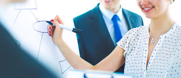 Businesswoman writing on flipchart while giving presentation to colleagues in office Stock Photo