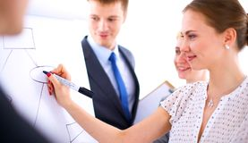 Businesswoman writing on flipchart while giving presentation to colleagues in office.  Stock Image