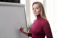 Businesswoman writing on flipchart while giving presentation to. Colleagues standing in office. Marker pen writing in flipchart. Business lady Stock Image