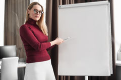 Businesswoman writing on flipchart while giving presentation to. Young businesswoman writing on flipchart while giving presentation to colleagues standing in Royalty Free Stock Photography