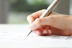 Businesswoman writing on a form Stock Images