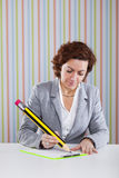 Businesswoman writing with a giant pencil Royalty Free Stock Photo