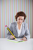 Businesswoman writing with a giant pencil Royalty Free Stock Images