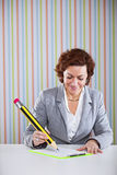 Businesswoman writing with a giant pencil Stock Photography