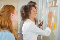 Businesswoman writing on glass as colleagues looking at it Stock Image