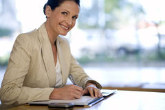 Businesswoman writing in her agenda Stock Photography