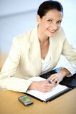 Businesswoman writing in her agenda Royalty Free Stock Image