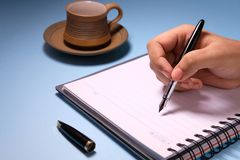 Businesswoman writing in her agenda and cup of a tea on background.  Royalty Free Stock Photo
