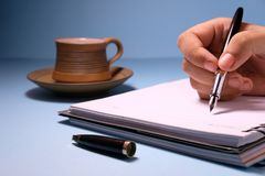 Businesswoman writing in her agenda and cup of a tea on background.  Royalty Free Stock Images