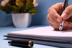 Businesswoman writing in her agenda in er office desk.  Royalty Free Stock Images
