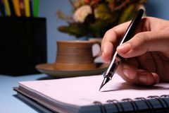Businesswoman writing in her agenda in her office desk.  Royalty Free Stock Photography