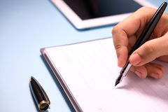 Businesswoman writing in her agenda and Ipad on background.  Royalty Free Stock Photography