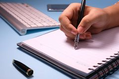 Businesswoman writing in her agenda and keybord on background.  Royalty Free Stock Photography