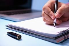 Businesswoman writing in her agenda and laptop on background.  Royalty Free Stock Photo