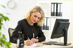 businesswoman writing on her workplace in office Stock Photography