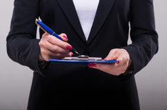 Businesswoman writing in ink on the clipboard. Closeup, grey background Royalty Free Stock Photography
